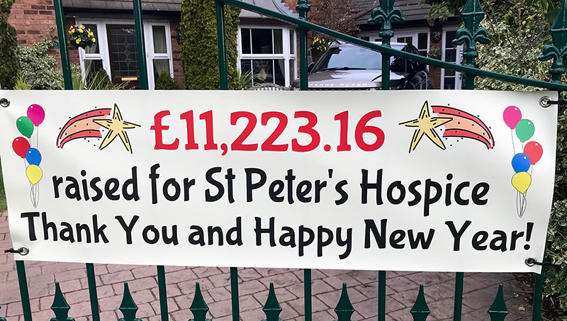 Photo of a banner hanging on a gate, announcing the final amount of £11,223 raised for St Peter's Hospice.