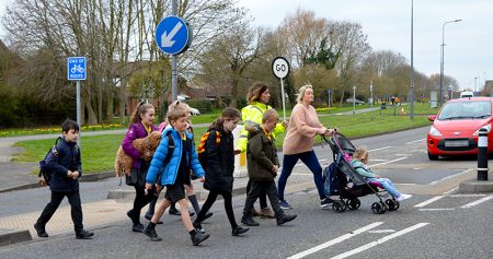 Photo of Esther Huke guiding children and parents over the uncontrolled crossing point.