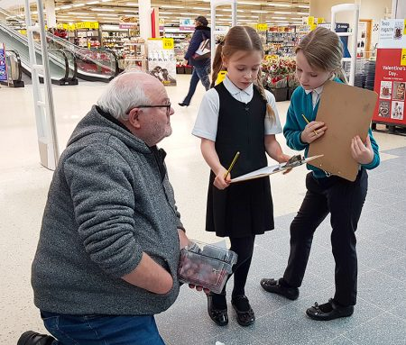 Photo of pupils interviewing a shopper as part of their survey work.