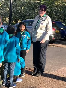 Photo of Donna Carl standing in front of a group of Beaver Scouts.