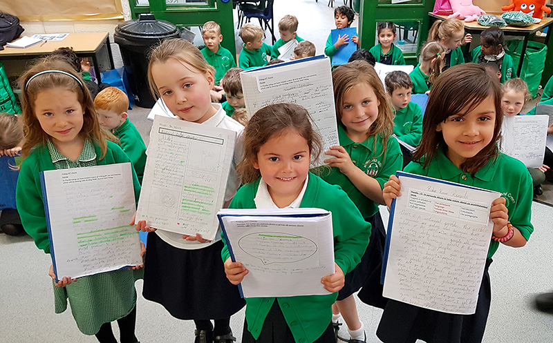 Photo of pupils proudly displaying their written work at the end of the presentation.