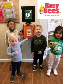 Photo of children pointing out the setting's newly installed defibrillator.