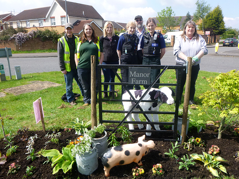 Photo of a group of people celebrating the return of 'Debbie the heifer' and 'Peppa the pig' to Manor Farm Roundabout.