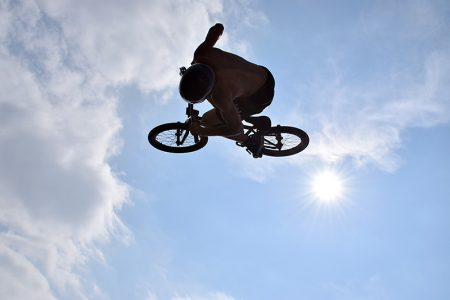 Photo of a BMX rider at the peak of a jump, with blue sky and the sun in the background.