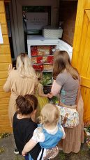 The first visitors make their selections from the produce in the fully stocked fridge.