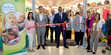 Photo of Chris Judd cutting the ribbon, assisted by store manager Simon George.