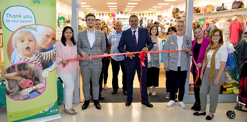 Chris Judd (CHSW head of retail) cuts the ribbon, assisted by store manager Simon George (on right, in striped jacket).