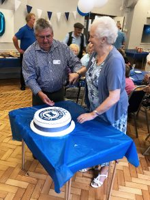 Photo of Dennis Rogers and guest of honour Shirley Holloway cutting the 20th anniversary cake.