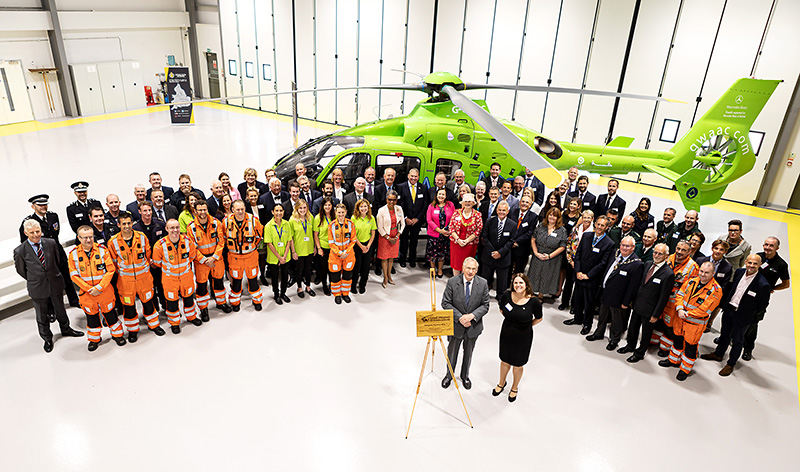 Photo of a large group of attendees standing in front of the air ambulance.