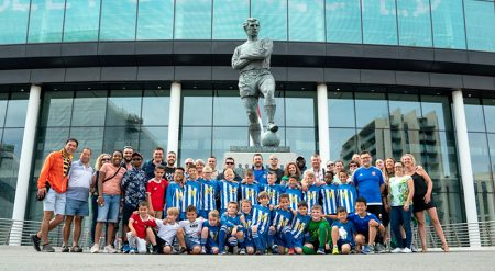 Photo of BSYFC U10 Blues team players, families and club officials grouped around the Bobby Moore Sculpture at Wembley Stadium.
