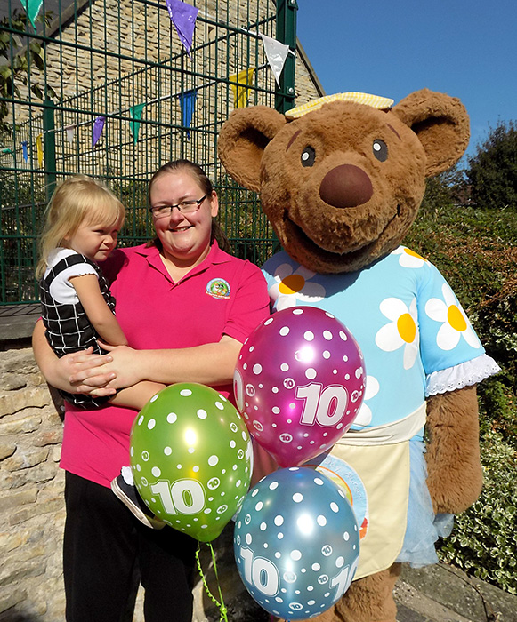 Photo of Bethan Jones holding a child and standing next to the Mama Bear's character.