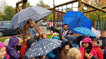 Photo of Mayor Tom Aditya cutting a ceremonial ribbon to officially open the new play equipment.