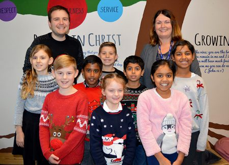 Photo of teachers and pupils at Holy Trinity Primary School celebrating their recent 'good' grading by Ofsted.