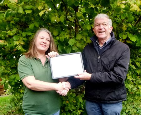 Photo showing an It's your Neighbourhood 'Gold' award certificate being presented to Sara Messenger.