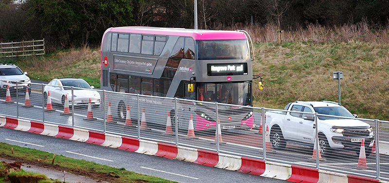 Photo of an M1 MetroBus vehicle stuck in a queue of traffic on the approach to Great Stoke Roundabout.