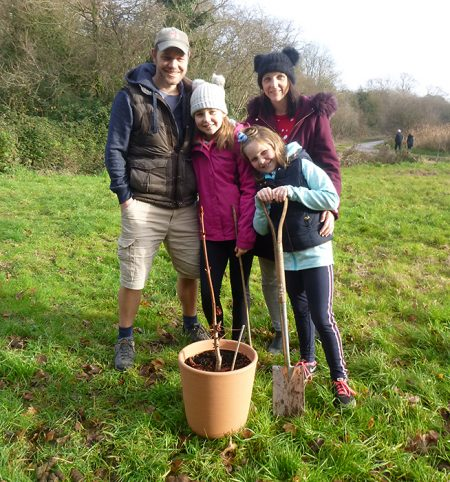 Photo of the Edgely family planting their sapling.