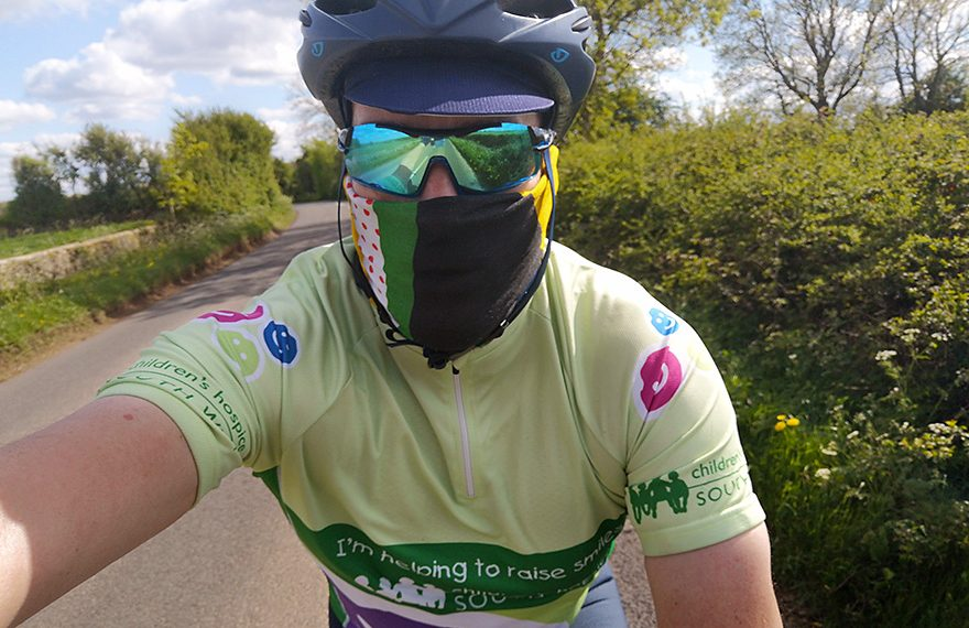Photo of Rob Berry, wearing sun glasses and a face mask, on his bike.
