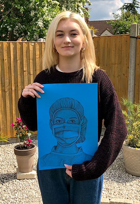 Photo of Jess holding her drawing.