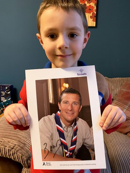 Photo of Henry holding a signed photo of Bear Grylls.