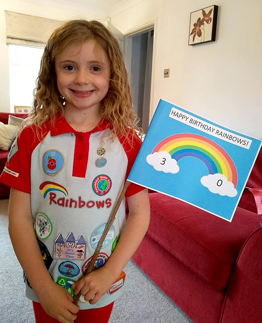 Photo of a Rainbow Guide celebrating the unit's 30th birthday at home.