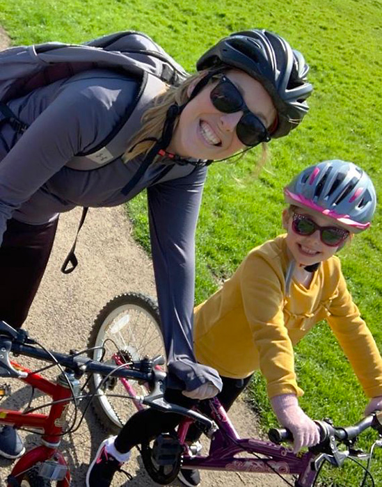Photo of Ella (accompanied by her mum) on a bike ride.