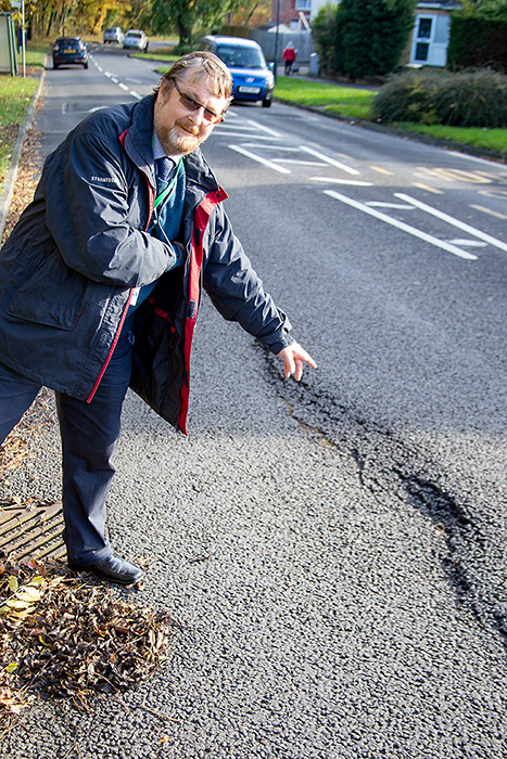 Photo of Cllr Keith Cranney pointing out a damaged road surface.
