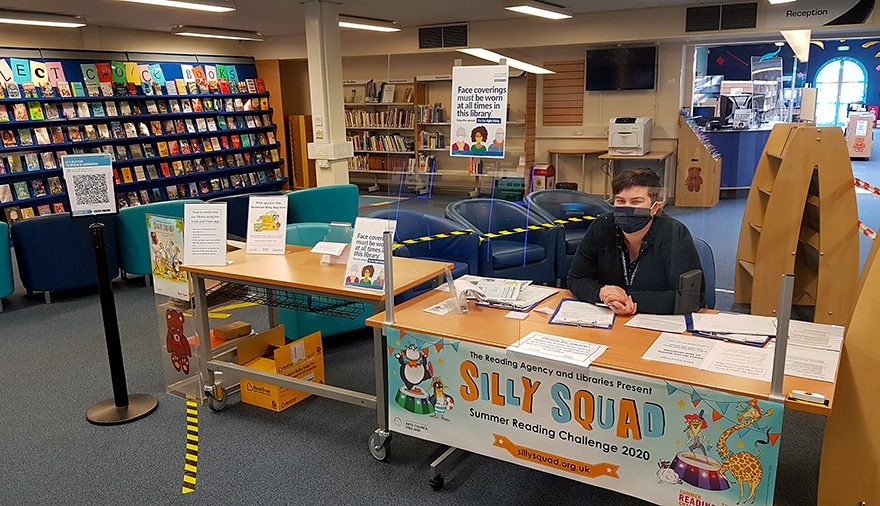 Photo of the inside of Bradley Stoke Library with a member of staff seated behind a screen and wearing a mask.