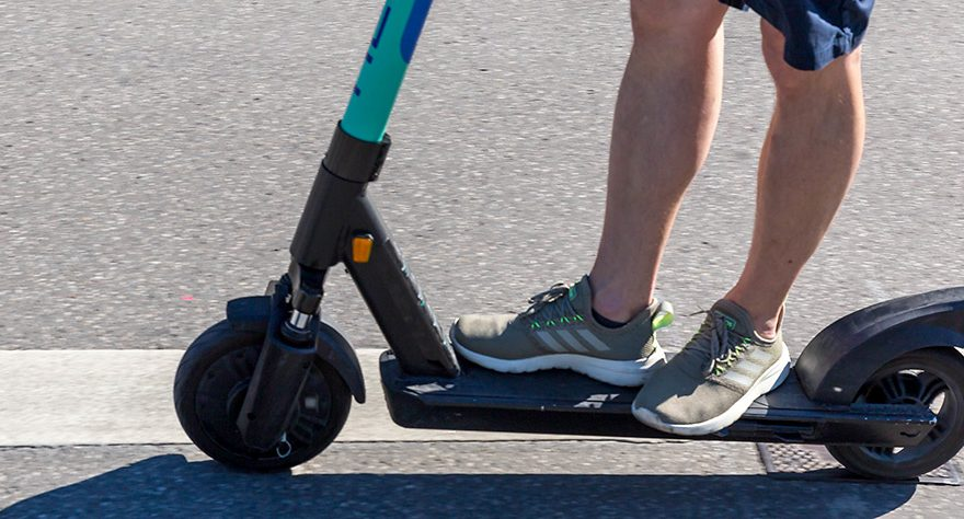 Photo of a man riding an e-scooter.