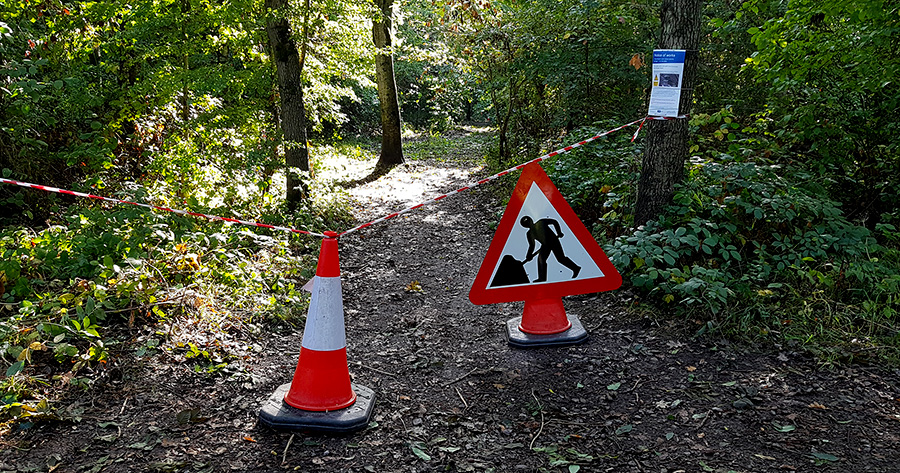 Photo of a taped-off path with a roadworks sign.