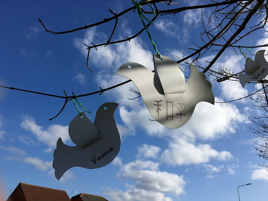 Photo of paper doves hanging from the branches of a tree.