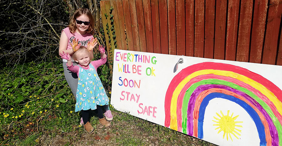 Photo of children with a rainbow banner.