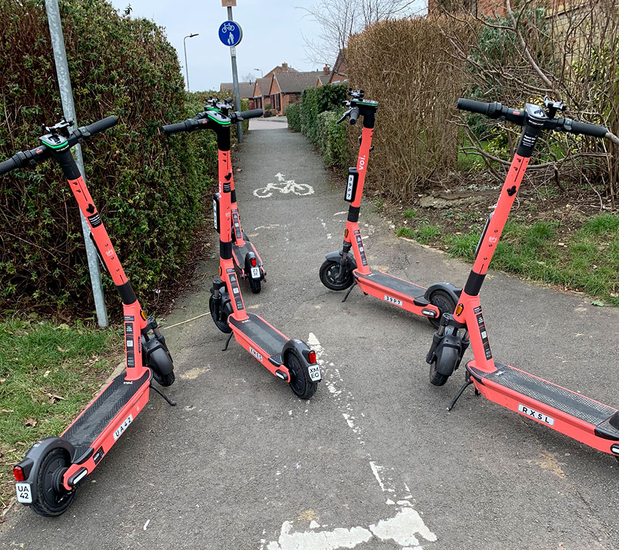 Photo of Voi e-scooters blocking a path.