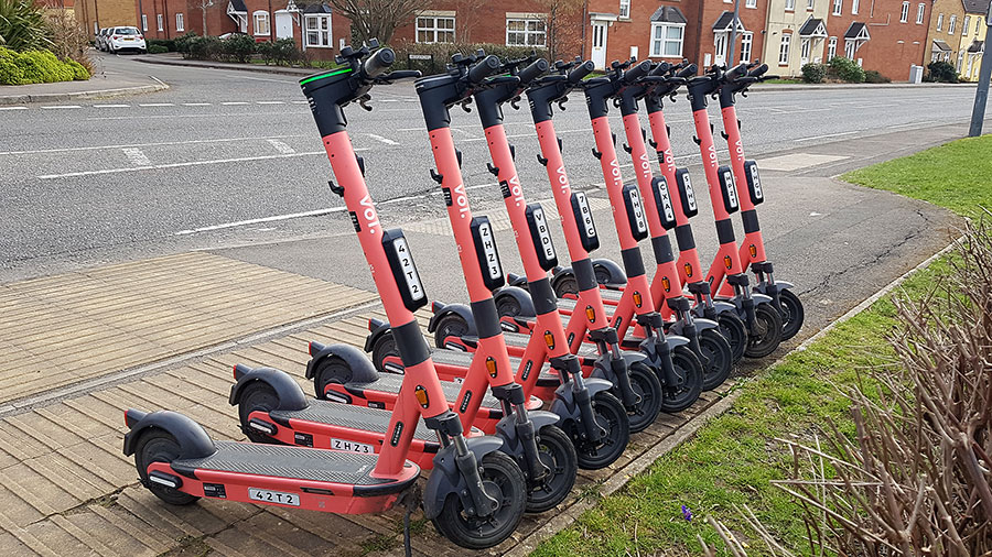 Photo of a row of Voi scooters.