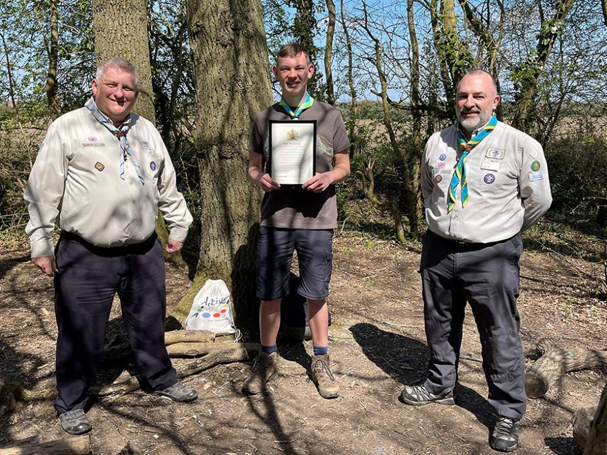 Photo of a Scout holding a certificate flanked by two Scout leaders.