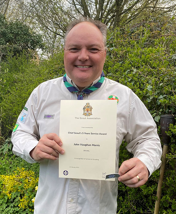 Photo of a Scout leader holding a certificate.