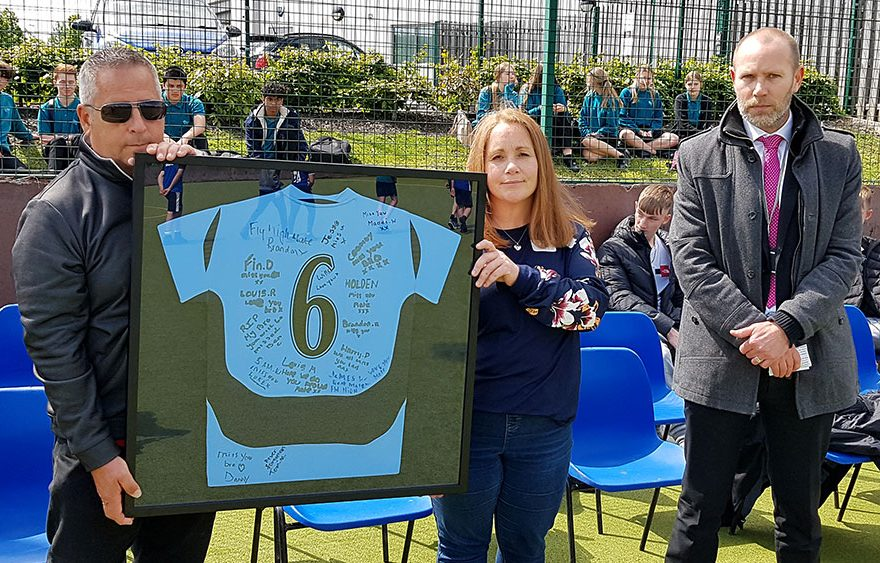 Photo of two people holding a framed football shirt.