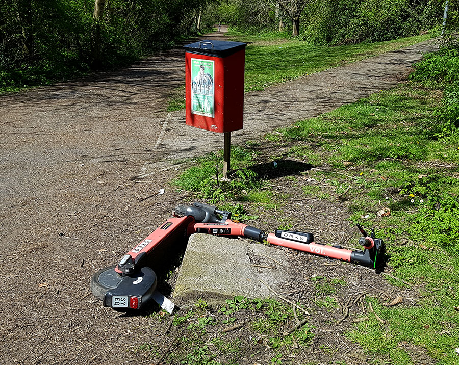 Photo of a dumped e-scooter lying at the side of a footpath.