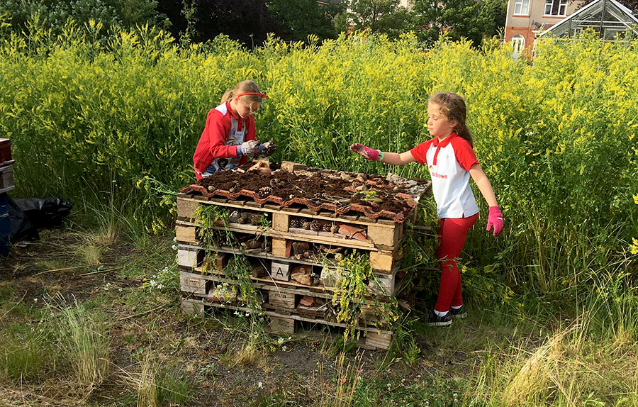 Photo of two children with a stack of pallets.