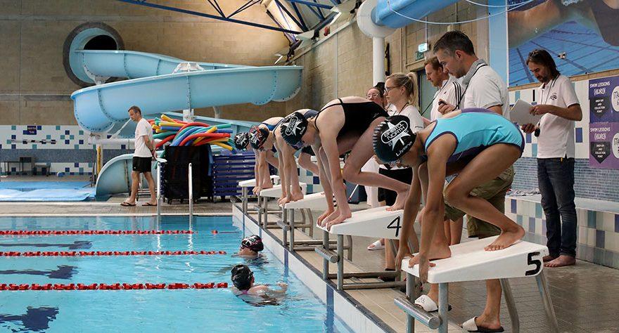 Photo of swimmers standing on start blocks.