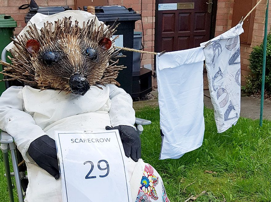 Photo of a scarecrow in the form of a seated hedgehog wearing clothes.