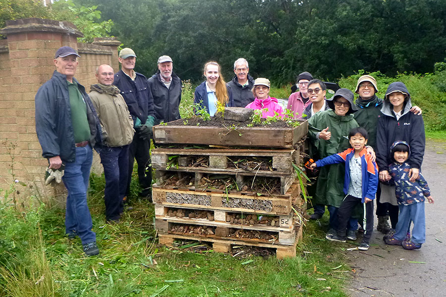 Photo of a group of people standing around a bug hotel constructed from wooden pallets.