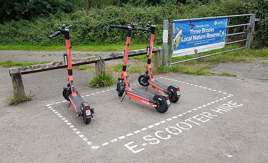 Photo of three e-scooters within a parking bay marked on the ground.